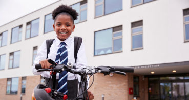 School pupil with her bike outside a school
