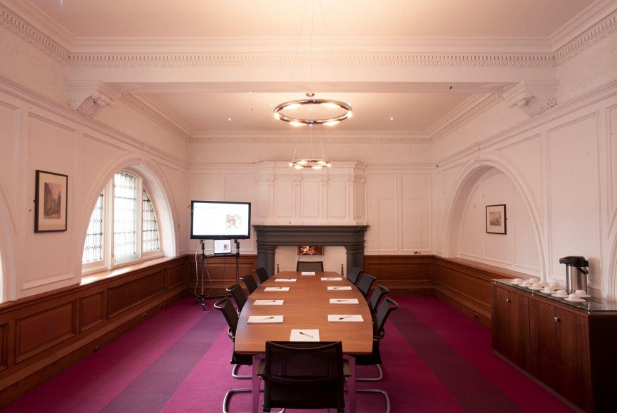 A bright boardroom with panelled walls and a long desk with four chairs on either side and one at either end. There is a tea station at one wall with an urn and several cups and saucers. At the far wall there is a large plasma on a stand with a laptop stand below.