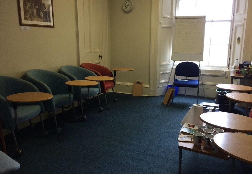 Meeting room with eight chairs with attached writing desks lined up against opposite walls and another chair and flipchart at the head of the room, behind which is a table with tea and coffee supplies.
