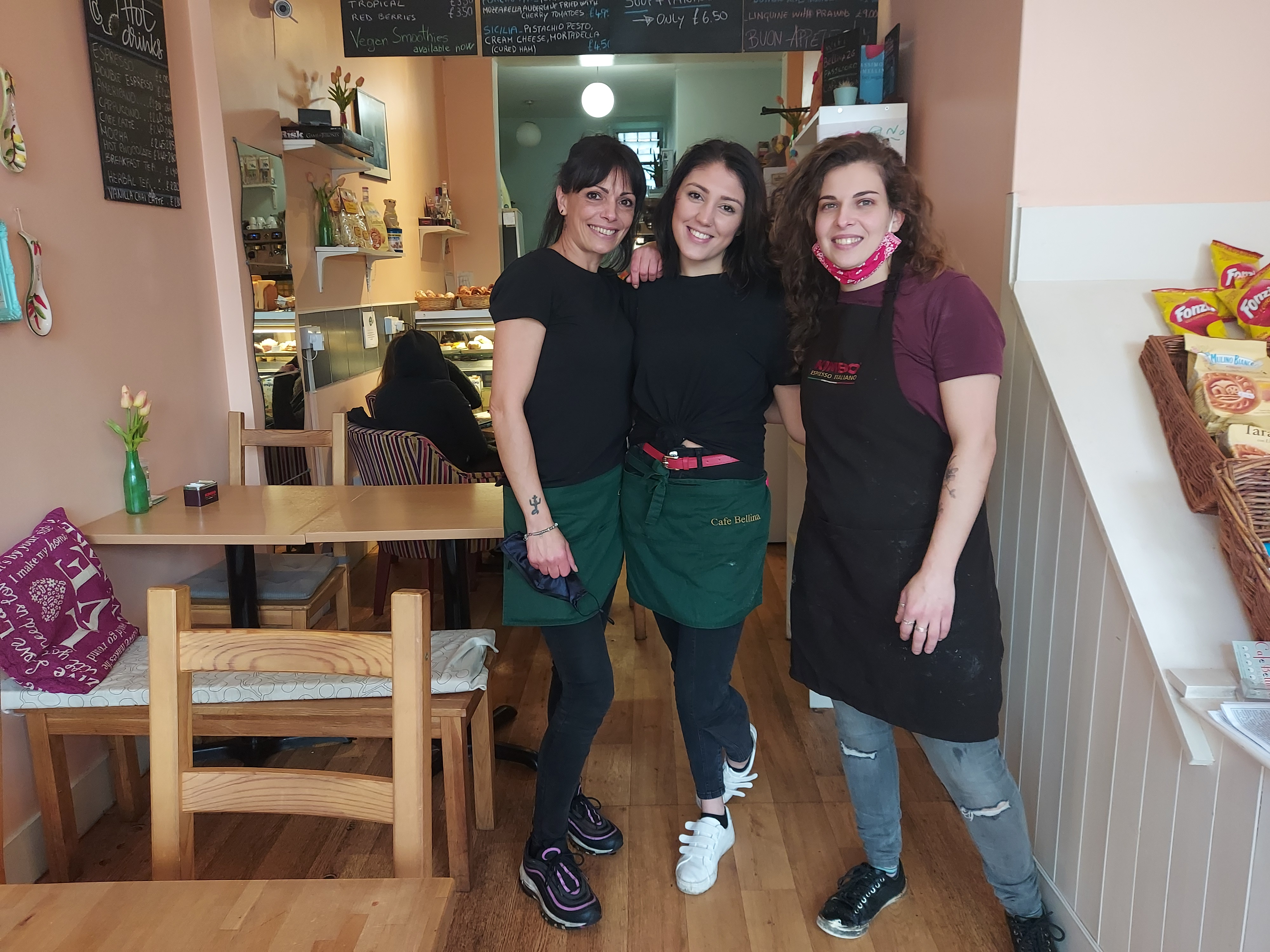 Three women standing inside Cafe Bellina.