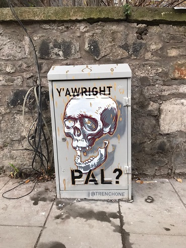 Mural painted by Trench One on a utility box which has a skull and the slogan Y'alright Pal? painted on it.