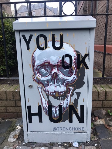 A mural painted on by artist Trench One with a skull present and 'You OK Hun?' painted on it.